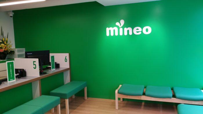 緑の大きな壁にmineoのロゴ